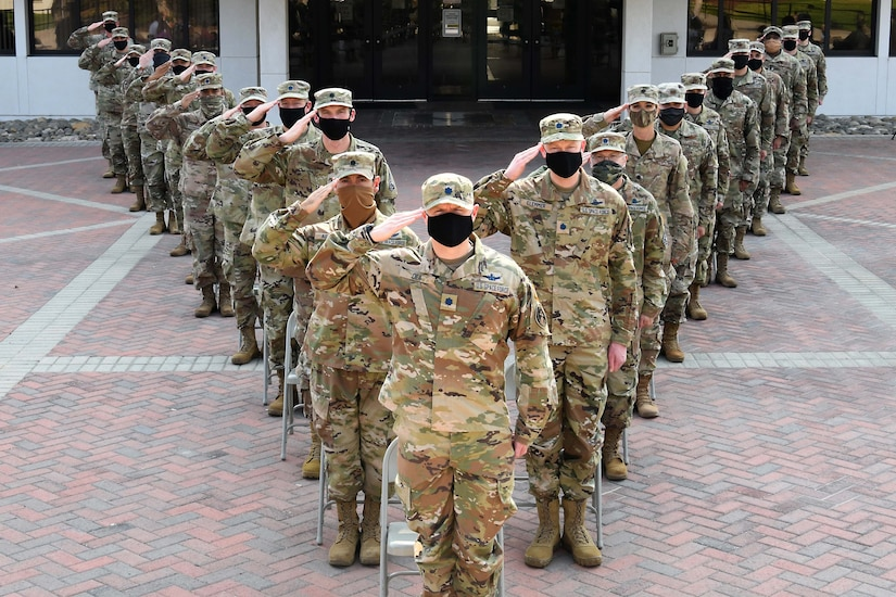 Service members wearing face masks stand in formation.