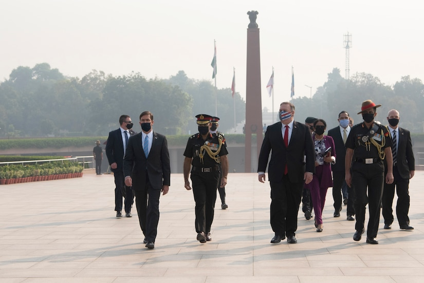 Defense Secretary Dr. Mark T. Esper and Secretary of State Michael R. Pompeo walk with other officials at an outdoor monument.