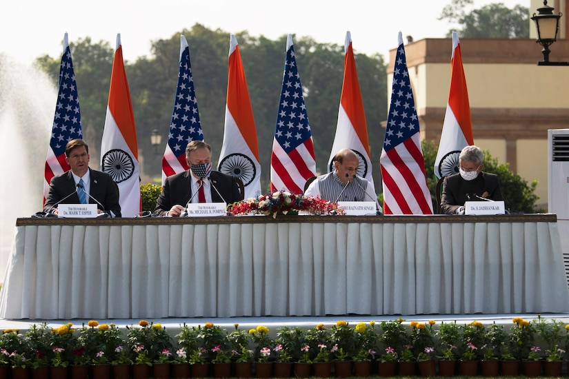 Defense Secretary Dr. Mark T. Esper and Secretary of State Michael R. Pompeo sit at a long table outdoors with their Indian counterparts.