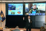Command director speaks in front of large screens.