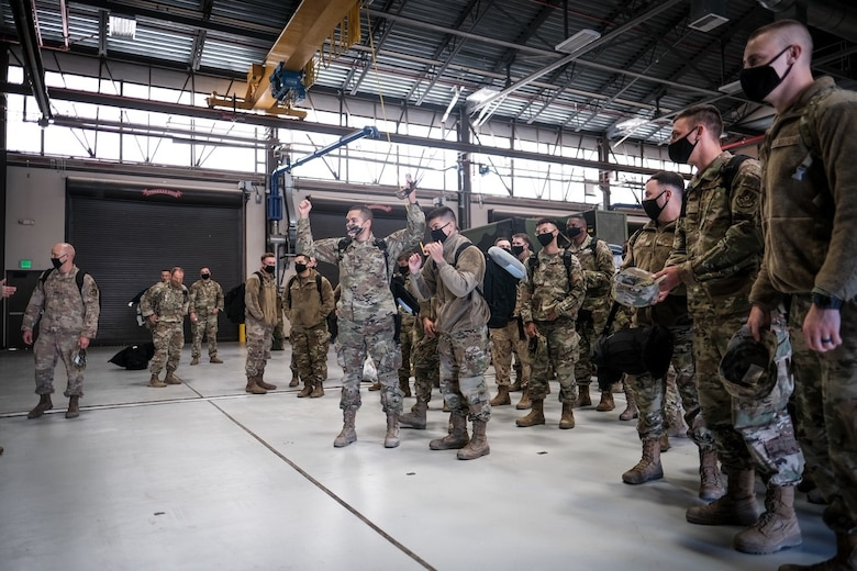 Airmen assigned to the 729th Air Control Squadron father in a hangar after returning home.