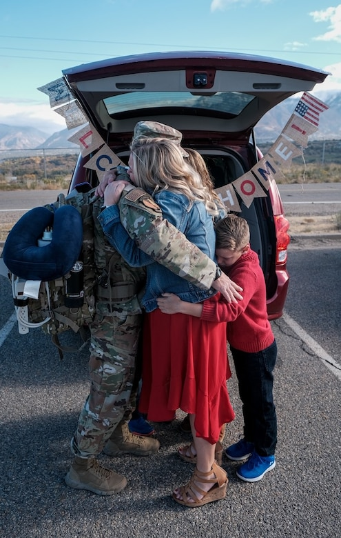 An Airman assigned to the 729th Air Control Squadron hugs his family members upon his returns home.