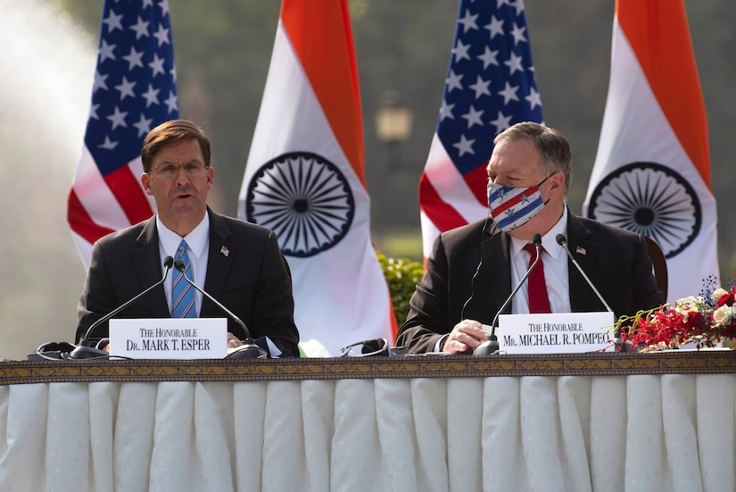 Defense Secretary Dr. Mark T. Esper sits and speaks at a table as Secretary of State Michael R. Pompeo looks on.