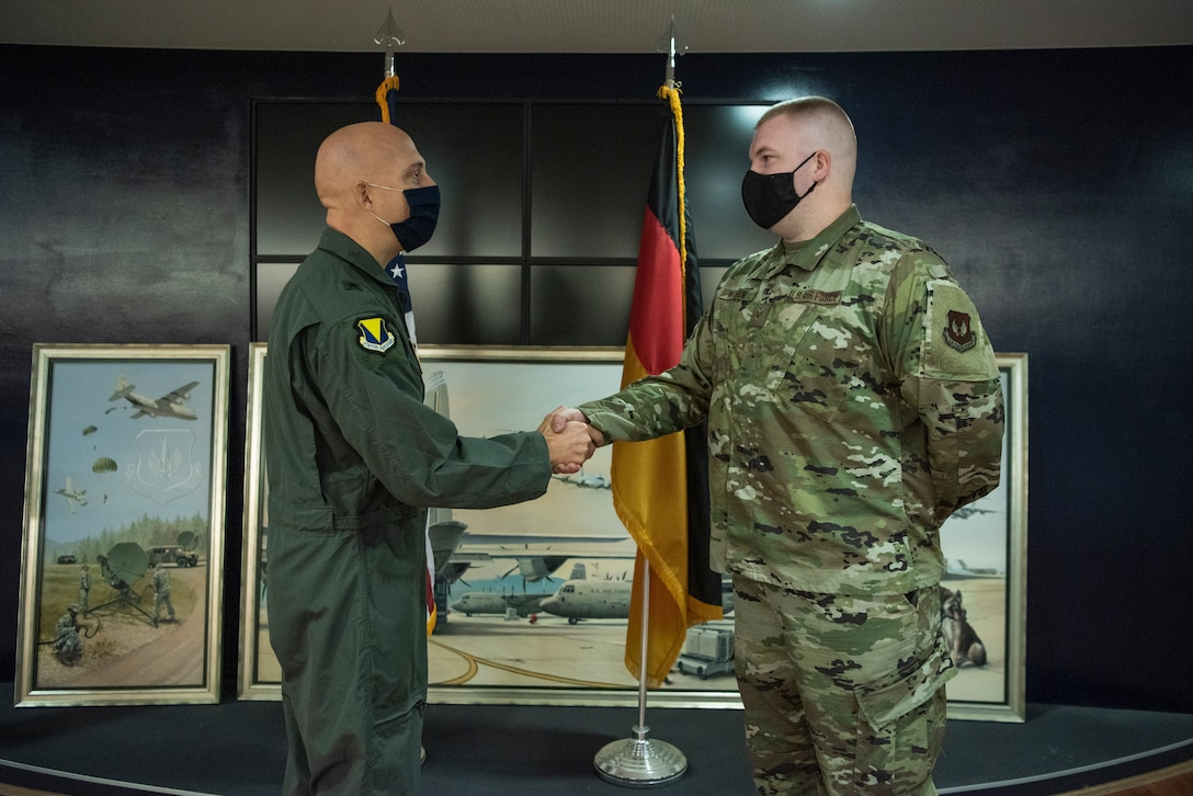 U.S. Air Force Staff Sgt. Tyler D. Nelson, 86th Maintenance Group maintenance operations center senior controller, receives a coin from Brig. Gen. Josh M. Olson, 86th Airlift Wing commander, at Ramstein Air Base, Germany, Oct. 23, 2020.