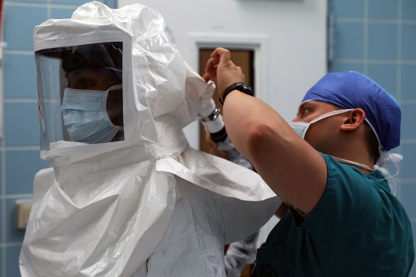 A medical technician wearing a face mask helps someone put on personal protective equipment.