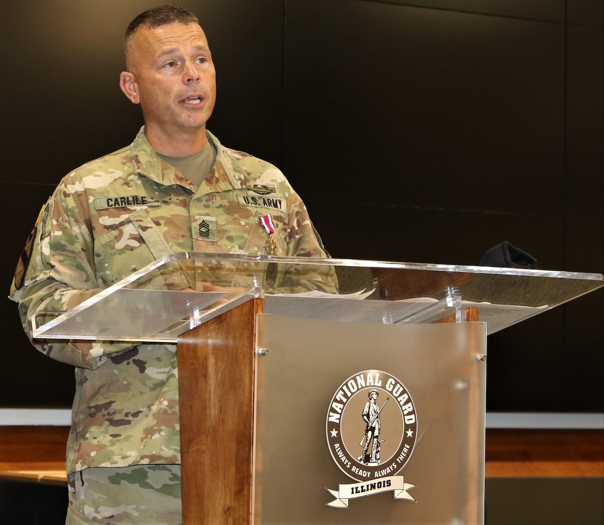 Master Sgt. Joshuah Carlile, of Bourbonnais, Illinois, addresses friends and family attending his retirement ceremony Sept. 12 at the Illinois Military Academy, Camp Lincoln, Springfield, Illinois.