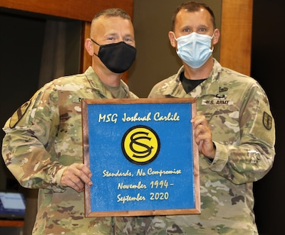 Maj. Kyle Scifert, of Elgin, Illinois, Commander, Illinois Army National Guard Officer Candidate School, presents Master Sgt. Joshuah Carlile, of Bourbonnais, Illinois, a gift from the Illinois Army National Guard Officer Candidate School