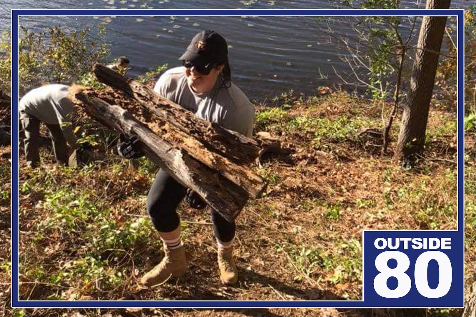 """Woman carries logs from river bank up a hill. Graphic reads """"Outside 80."""""""