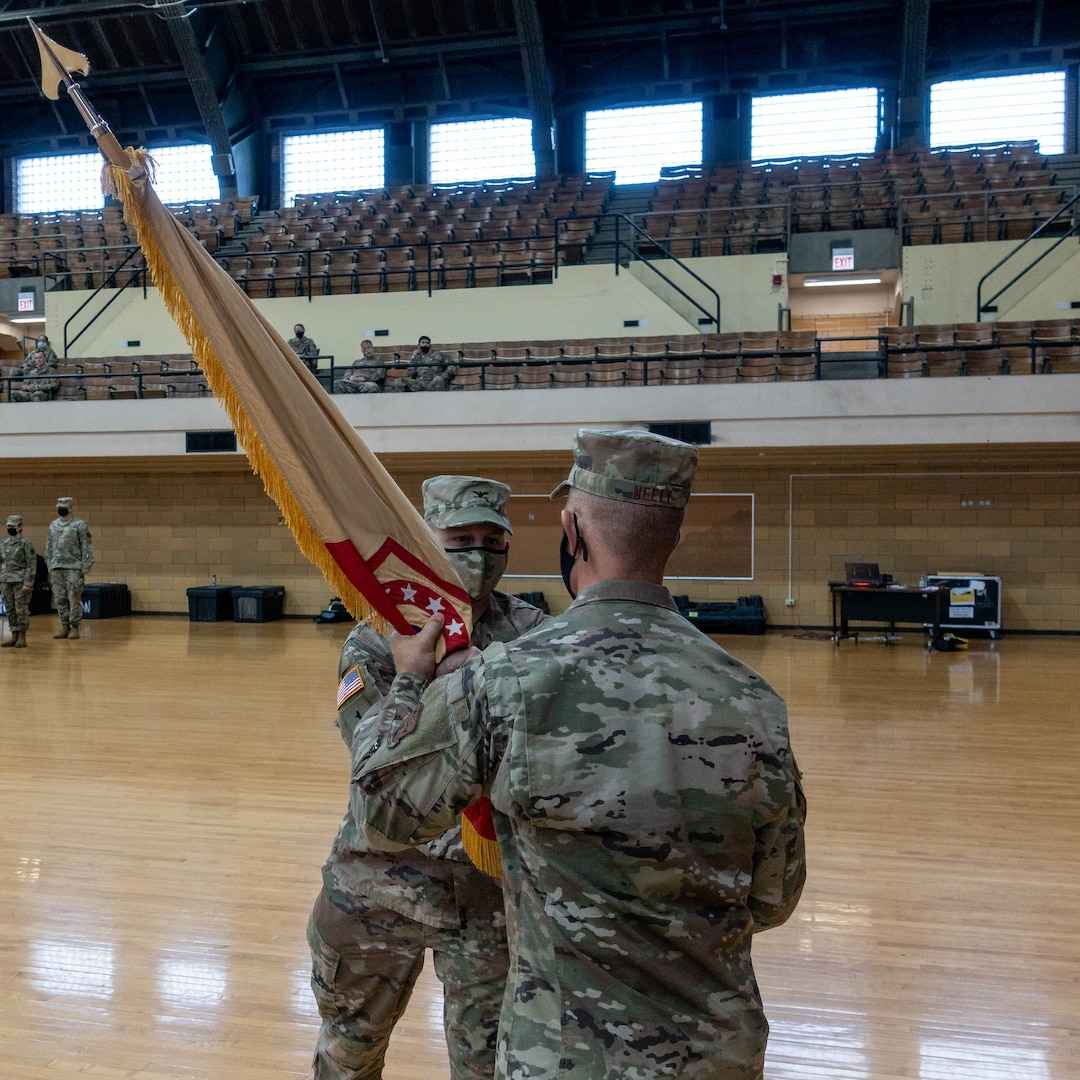 Col. Justin Osberg, Geneva, Illinois, hands the 108th Sustainment Brigade's guidon to Maj. Gen. Richard Neely, the Adjutant General, Illinois National Guard, at the Northwest Armory, Chicago, Illinois, Sept. 12