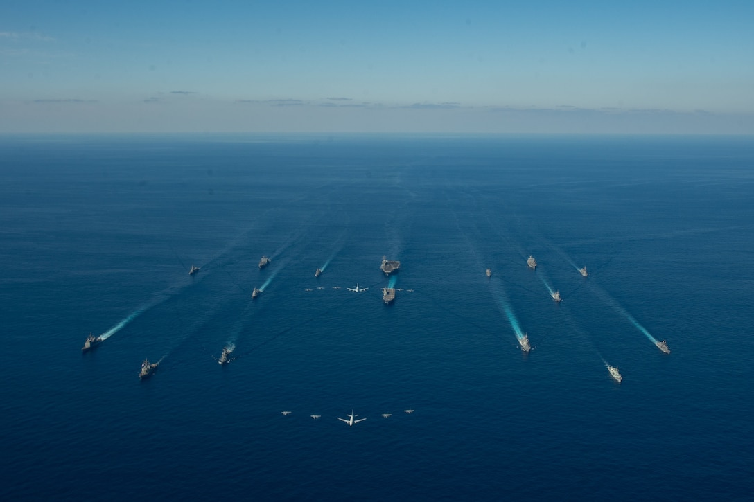 Multiple ships steam in formation across the water while aircraft fly above them.