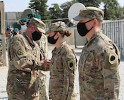 Lt. Col. Jason Osberg, of Champaign, Illinois, Commander, Bilateral Embedded Staff Team A25, presents Maj. Lorrie Novak, of Frankfort, Illinois, with her combat patch during the recent ceremony.