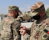Lt. Col. Jason Osberg, of Champaign, Illinois, Commander, Bilateral Embedded Staff Team A25, presents 1st Lt. Kurt Kuzur, of Tinley Park, Illinois, with his combat patch during the recent ceremony.