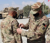 Lt. Col. Jason Osberg, of Champaign, Illinois, Commander, Bilateral Embedded Staff Team A25, presents Master Sgt. Adam Abdul, of Collinsville, Illinois, with his combat patch during the recent ceremony.
