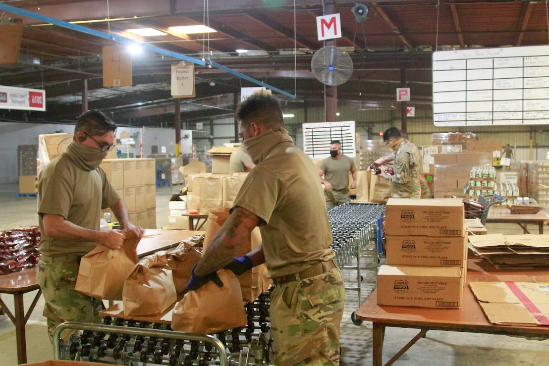 Soldiers put food in grocery bags at a warehouse.