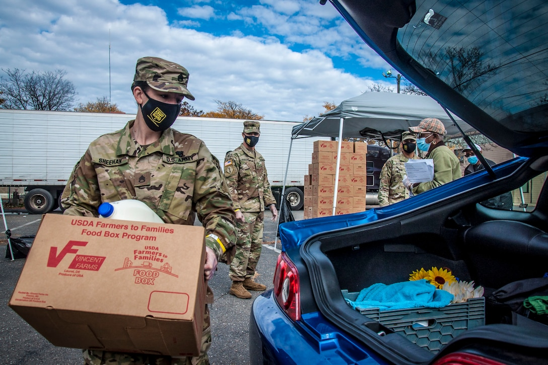 A soldier carries a box of food to the trunk of a car.