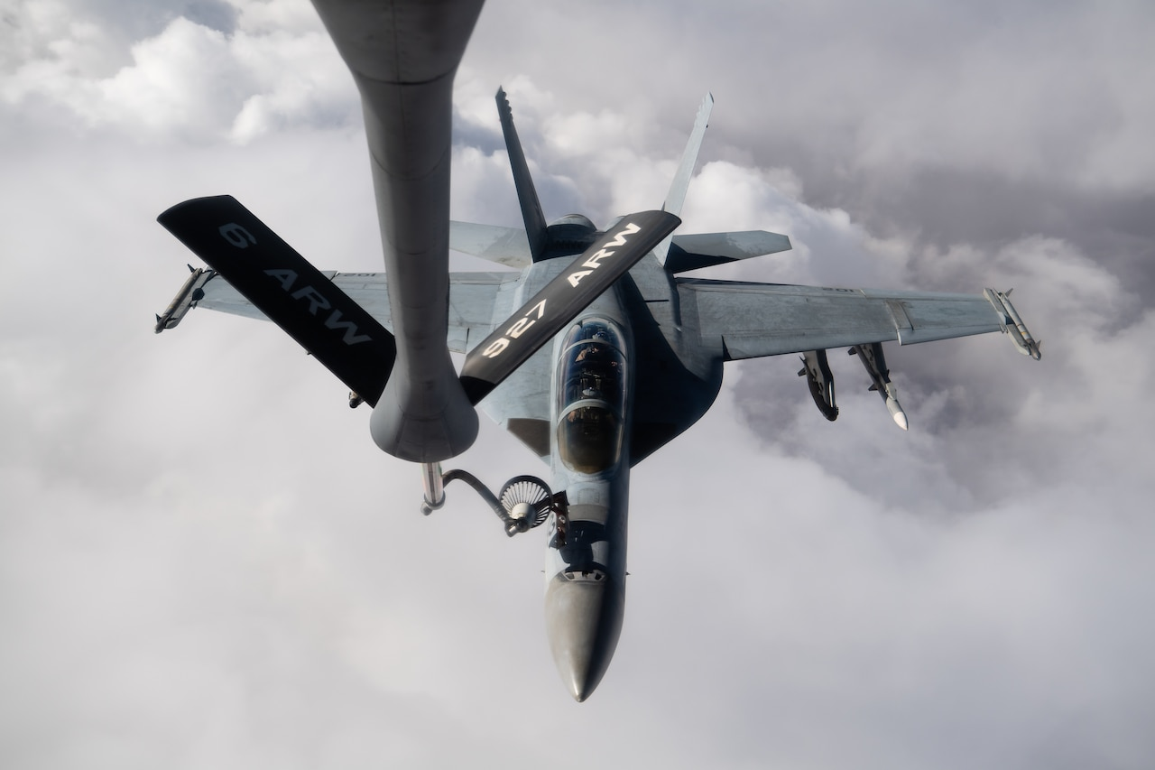 A long pole carrying fuel from a tanker aircraft attaches to a fighter jet while flying in clouds.