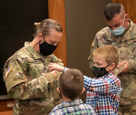Newly promoted Sgt. 1st Class Lindsey Gibbs' sons, Owen and Henry, place her new rank on her uniform as husband, CWO3 Brandon Gibbs places her new rank on her cap during her promotion ceremony at the Illinois Military Academy, Camp Lincoln, Springfield, Illinois Oct. 15.
