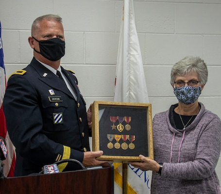 Kathy Andersen, of Roscoe, Illinois, great niece of the late Homer Stanger, accepts Stanger's returned medals