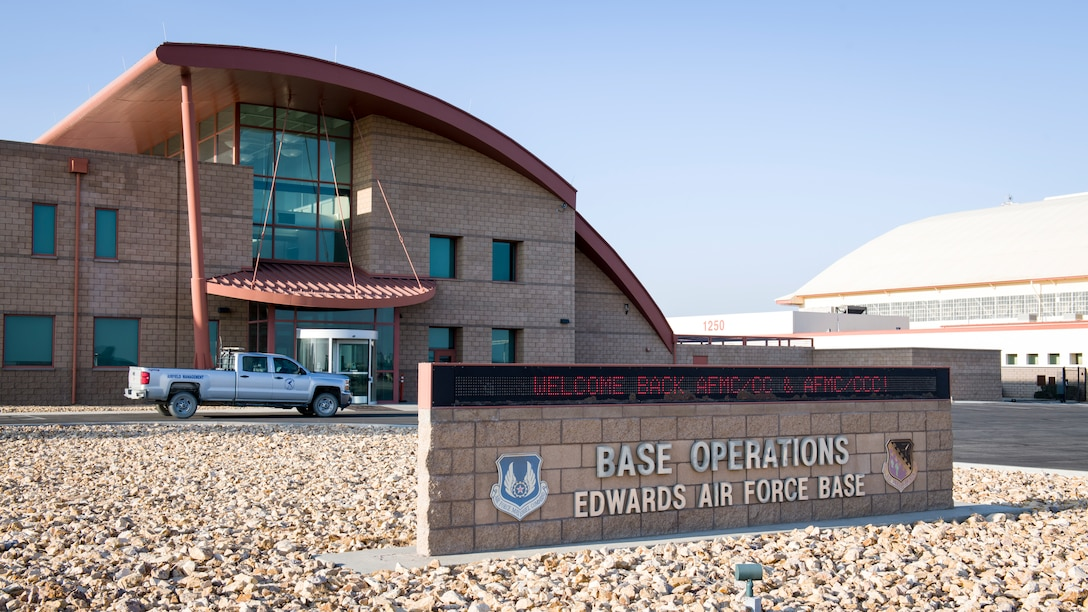 The Base Operations building welcomes Gen. Arnold W. Bunch, Jr., commander of Air Force Materiel Command, and Chief Master Sgt. Stanley Cadell, AFMC Command Chief, to Edwards Air Force Base, California, Oct. 23. (Air Force photo by Giancarlo Casem)