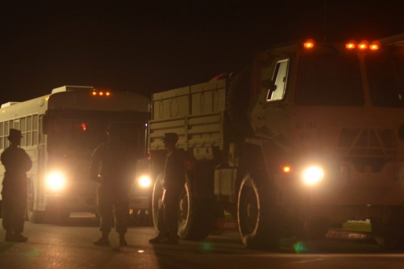 Service members stand near a bus and a military vehicle. It is dark outside.