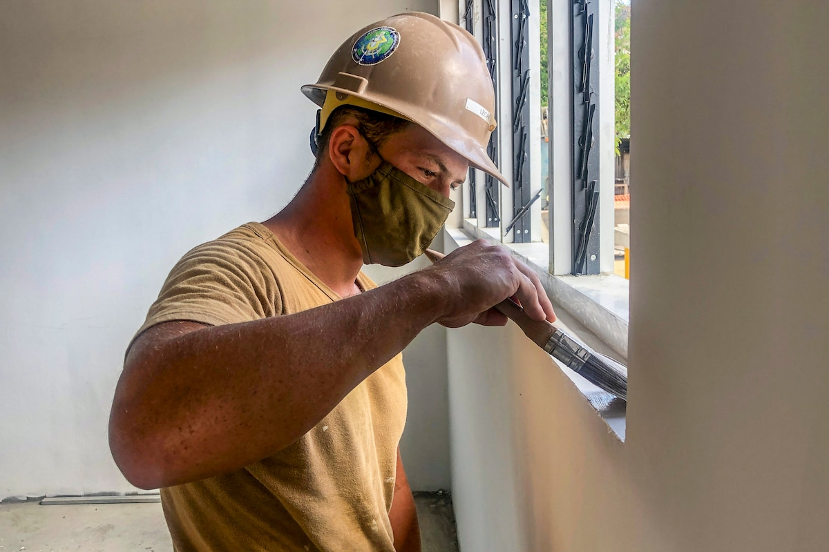 A sailor wearing a hardhat and face mask paints along a window ledge.