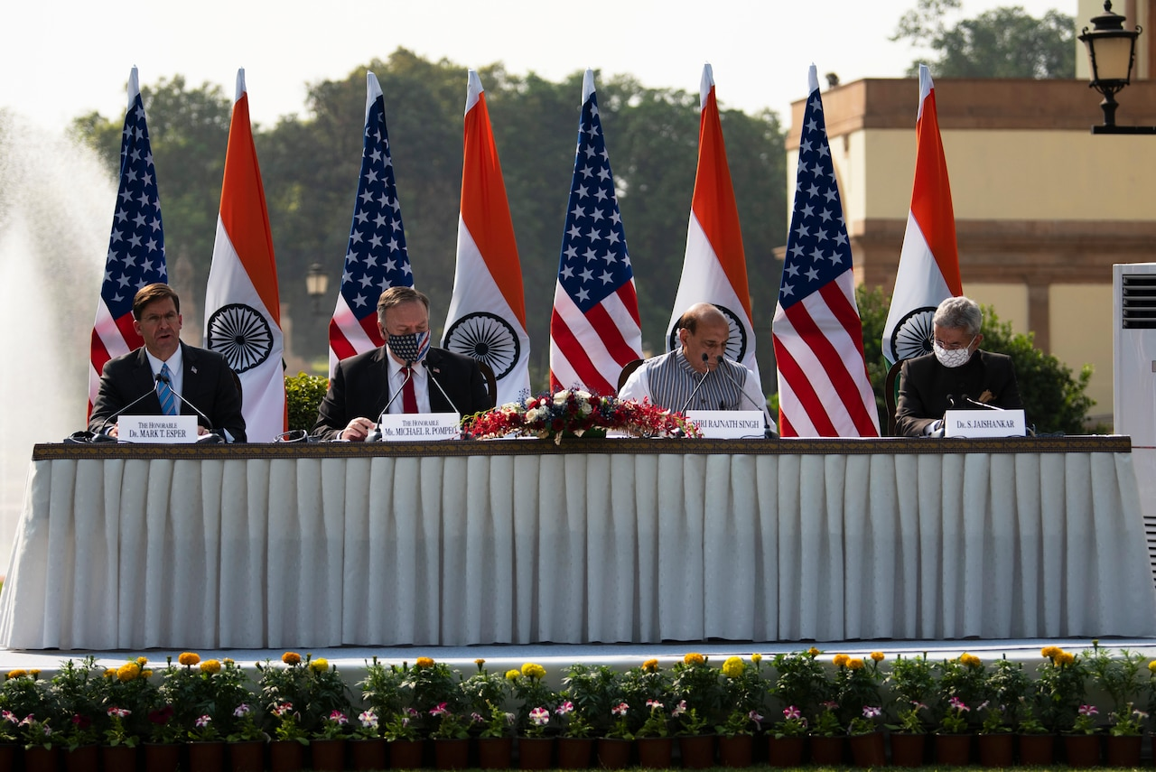 Four men sit outside at a table in front of U.S. and Indian flags.