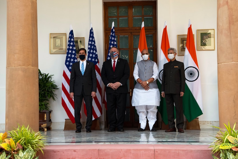 Four men wearing masks pose for a photo in front of the U.S. and Indian flags.