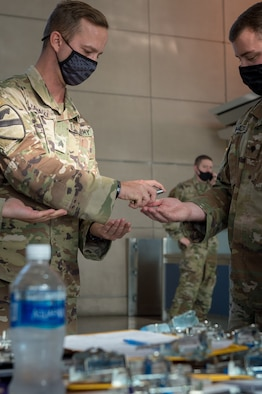 Army Sgt. Benjamin Zawacki and Spc. Kevin Hamilton, Soldiers assigned to 105th Military Police Company, Buffalo, N.Y., sanitize their hands between flight arrivals at Buffalo-Niagara International Airport Oct. 23, 2020. The team meets arriving passengers to distribute the State Department of Health traveler form to people coming from restricted states.