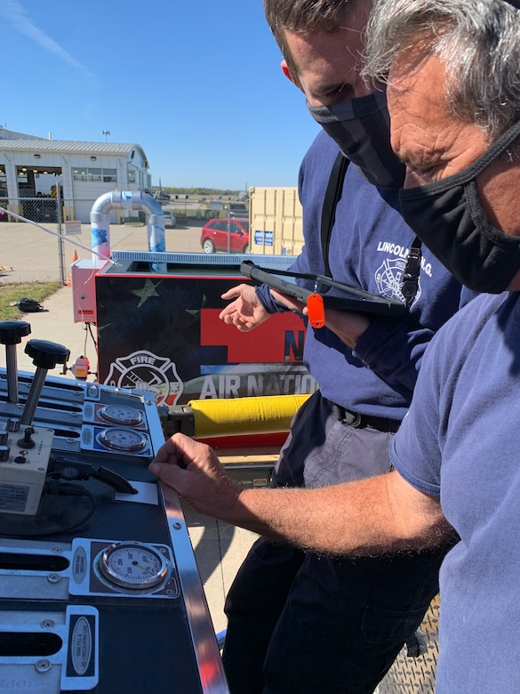 Firefighters Michael Budke and Craig Behrens, 155th Civil Engineering Squadron, run through a realistic fire scenario on a pump operations simulator Oct. 15, 2020, at Nebraska National Guard airbase in Lincoln, Nebraska. The squadron bought the simulator with the aid of U.S. Air Force innovation funds.
