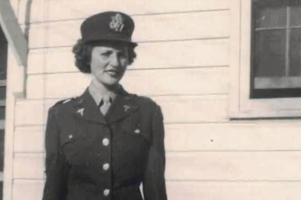 A woman wearing a military uniform poses for a photo.
