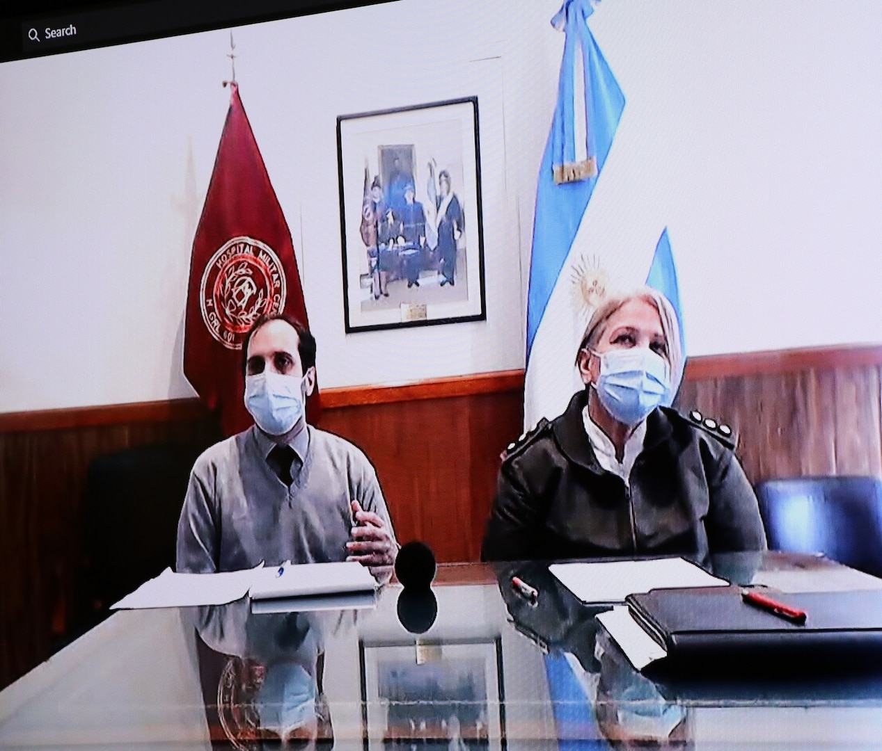 Argentine Army Col. Med Susana Pastor Arguello (right), Medical Director, Central Military Medical Hospital, Buenos Aires, Argentina, and translator Diego Blasco (left) answer COVID-19 questions during a video teleconference with Brooke Army Medical Center doctors Oct. 21.