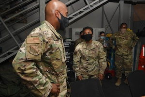 U.S. Air Force Staff Sgt. Shanita Davies. assigned to the 8th Expeditionary Air Mobility Squadron at Al Udeid Air Base, Qatar, guides the 379th Air Expeditionary Wing Command Chief, Chief Master Sgt. Kenneth Bruce, through her section of the 8th EAMS work center on Oct. 23, 2020. The Airmen of The Mighty Ocho are responsible for transporting an average of 10 million pounds of cargo and 5 thousand passengers throughout the U.S. Central Command area of responsibility each month, accounting for more than 36 percent of airlift operations in Europe and Southwest Asia. (U.S. Air Force photo by Staff Sgt. Kayla White)