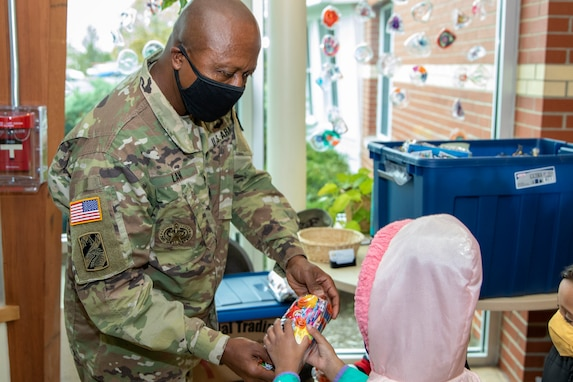 Command Sgt. Maj. Kenneth F. Law, U.S. Army Financial Management Command senior enlisted advisor, hands out a treat bag to a student at a childcare center located next to the Maj. Gen. Emmett J. Bean Federal Center Oct. 26, 2020. Law delivered more than 80 treat bags filled with candy and toys donated from USAFMCOM employees to give to the students, who typically parade through the Bean Center around Halloween each year. (U.S. Army photo by Mark R. W. Orders-Woempner)
