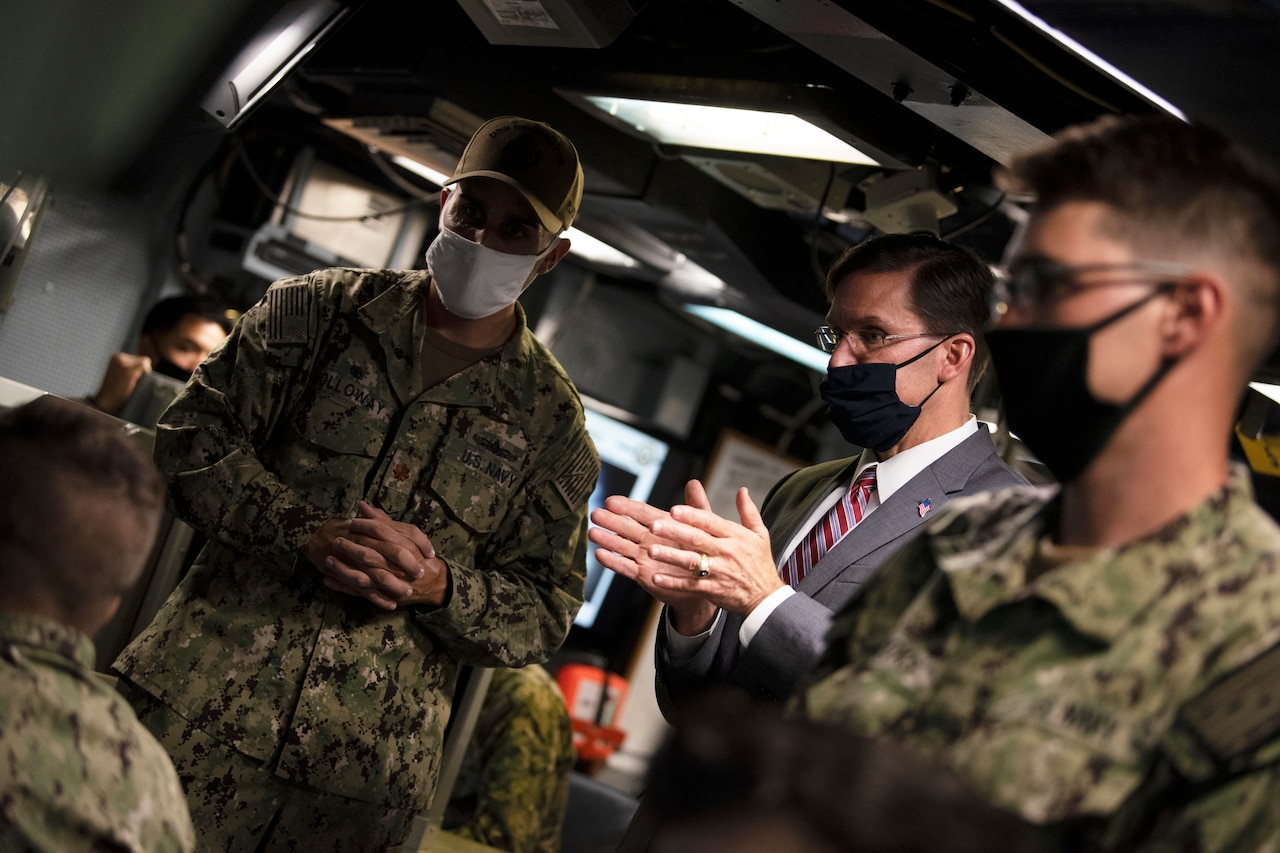 Defense Secretary Dr. Mark T. Esper speaks with service members on board a ship.