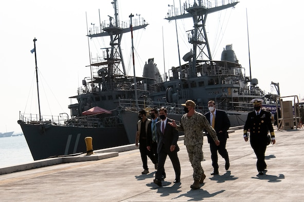 Defense Secretary Dr. Mark T. Esper stands with a group of service members.