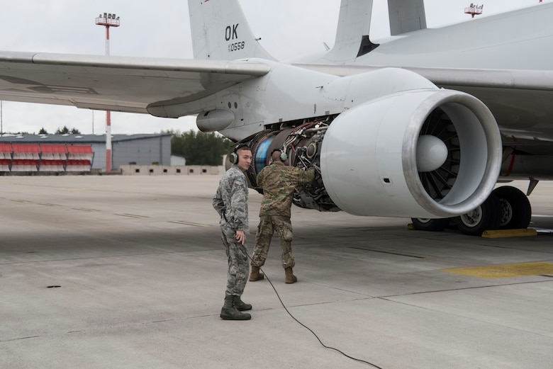 photo of two airman in front of a plane
