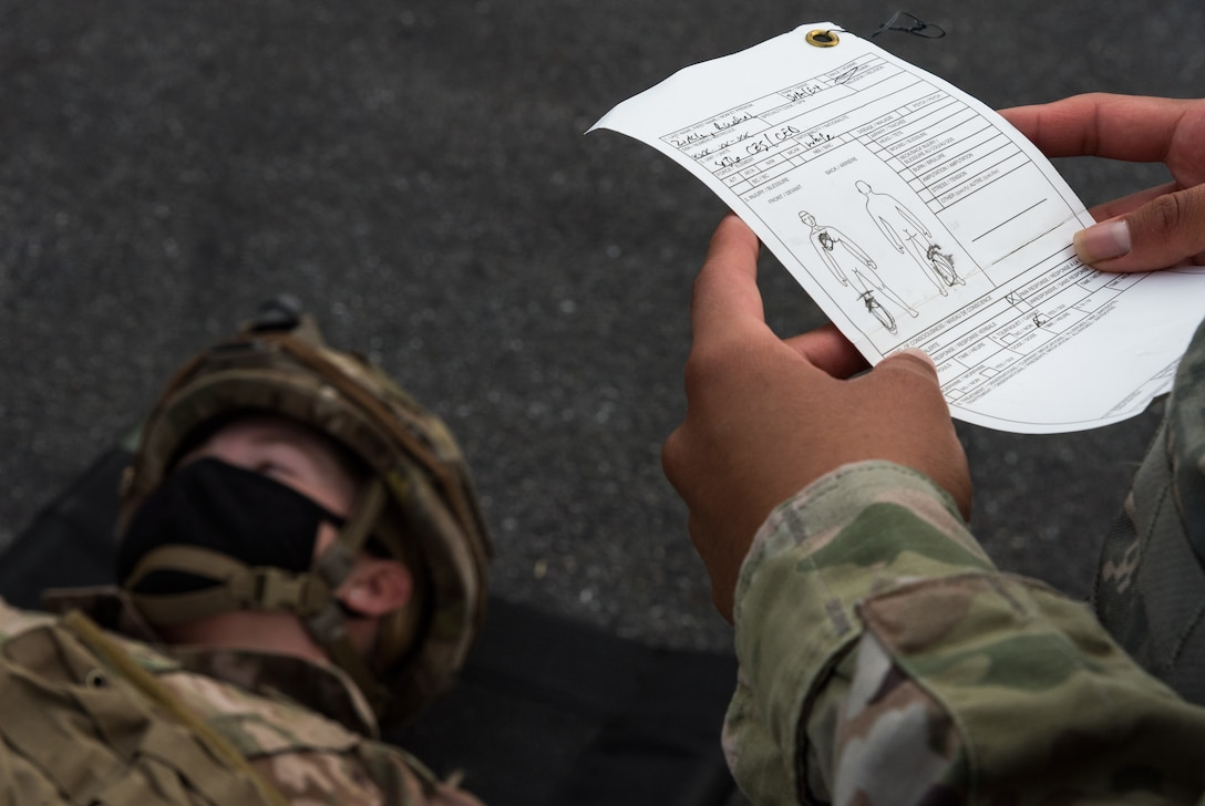 As part of a self-aid and buddy care training exercise, a 436th Civil Engineer Squadron Prime Base Engineer Emergency Force member reviews a tactical combat casualty care card identifying simulated injuries to Senior Airman Rachel Zirkle, 436th CES explosive ordnance disposal journeyman, Oct. 21, 2020, on Dover Air Force Base, Delaware. Sixty-four Prime BEEF members made up 10 teams in a 96-hour readiness exercise that included SABC, vehicle convoy techniques and land navigation exercises prior to arriving at the Tactics and Leadership Nexus. While at the TALN, they participated in night vision goggle familiarization; chemical, biological and radiological and nuclear defense training; individual movement techniques; and defense fighting position exercises. (U.S. Air Force photo by Roland Balik)