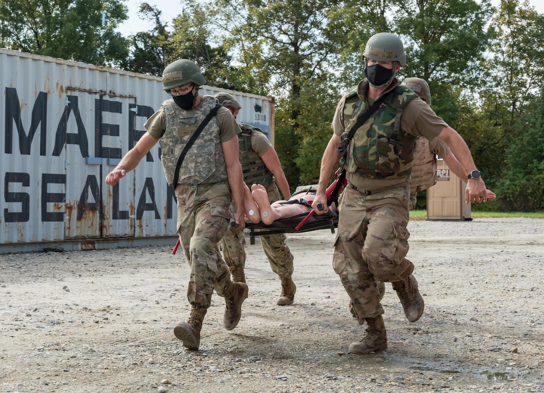 Four 436th Civil Engineer Squadron Prime Base Engineer Emergency Force members carry a mannequin on a stretcher after navigating through numerous Conex obstacles Oct. 21, 2020, at Tactics and Leadership Nexus on Dover Air Force Base, Delaware. Sixty-four Prime BEEF members made up 10 teams participated in a 96-hour readiness exercise that included self-aid and buddy care, vehicle convoy techniques and land navigation prior to arriving at the TALN. While at TALN, they participated in night vision goggle familiarization; chemical, biological and radiological and nuclear defense training; individual movement techniques; and defense fighting position exercises. (U.S. Air Force photo by Roland Balik)