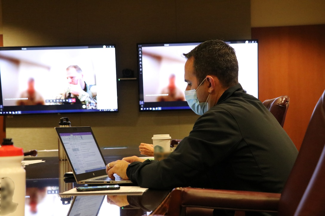 A man in a uniform is working on a laptop at a conference table. Screens in the background indicate that others are participating virtually.