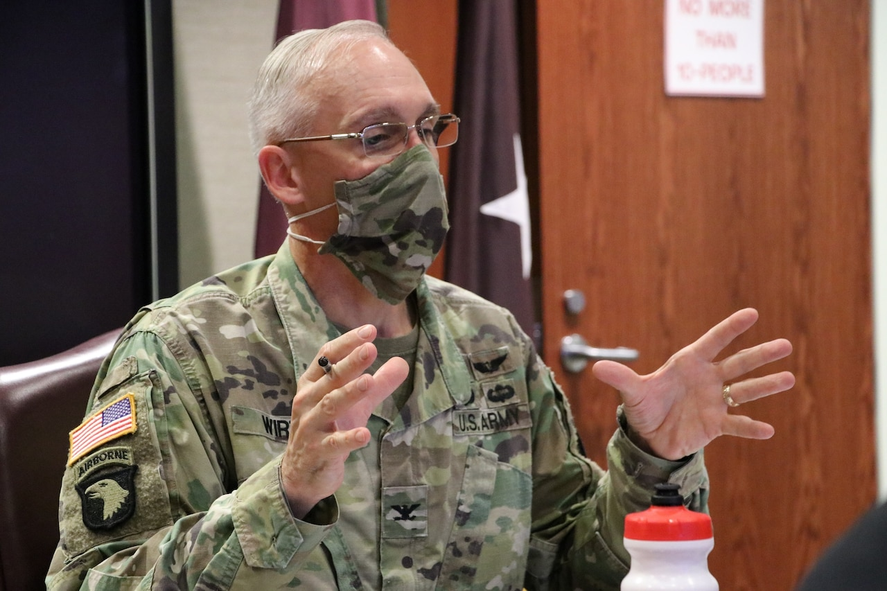 A man in a uniform and a face mask gestures while speaking.