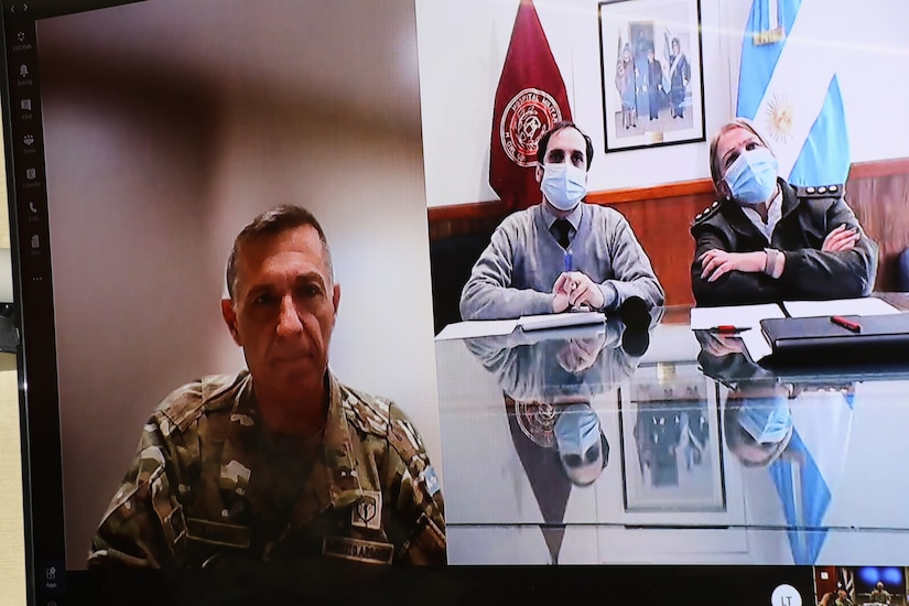A man in a military uniform is shown on the left side of the picture and a civilian and an officer from a foreign country are shown on the screen to his left.