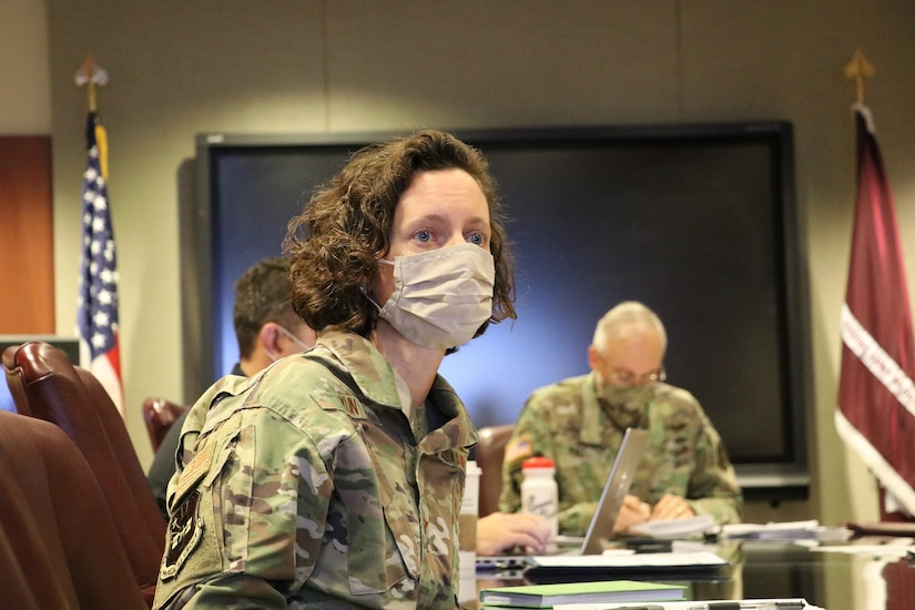 A woman in a military uniform and wearing a face mask participates in a discussion. Two other participants are in the background.