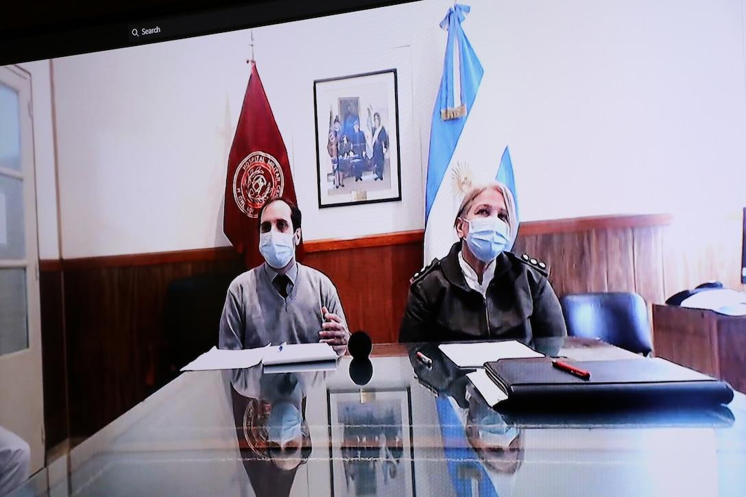 A civilian and a woman officer from a foreign army appear on a teleconference screen. Two flags from foreign entities are in the background.