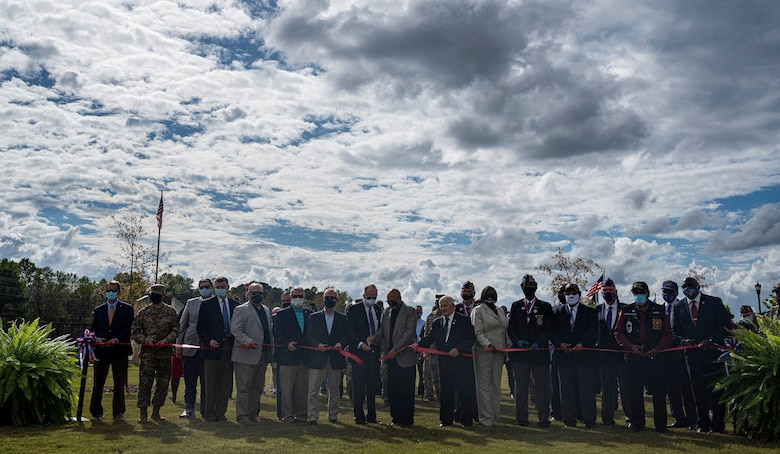A group of people gather to cut a ribbon.