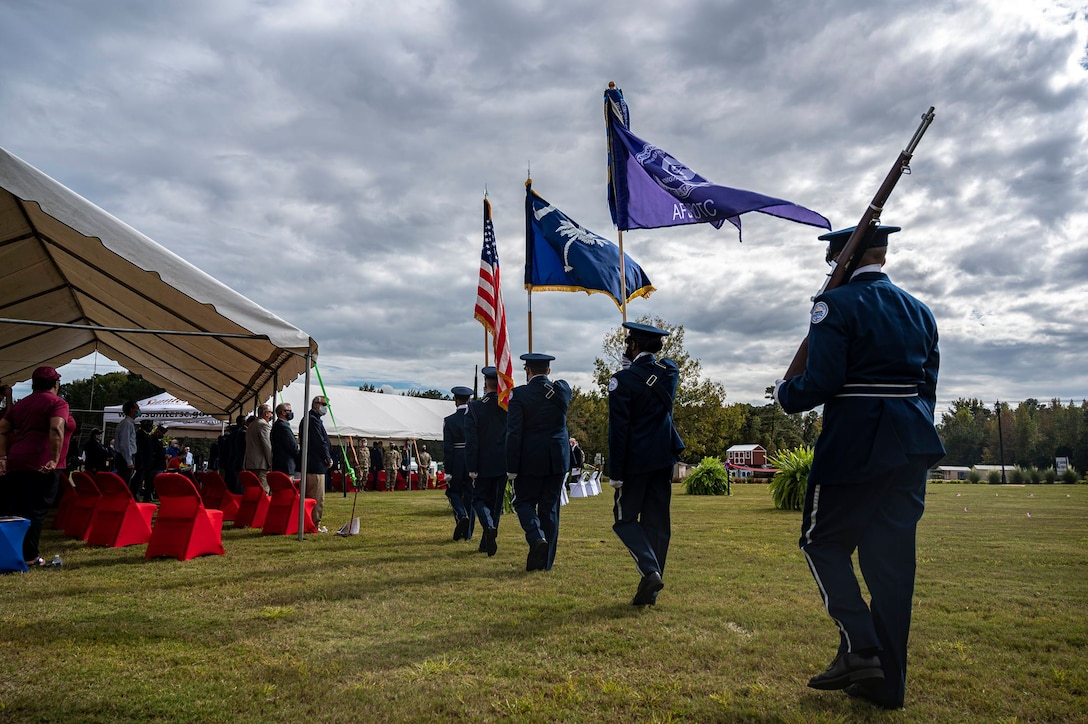 A color guard marches on a field during a ceremony.