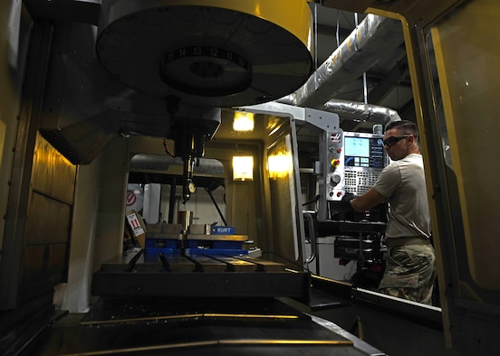 Staff Sgt. Tim Bergin, a 33rd Maintenance Squadron Fabrication Flight metals technician shift lead, employs computerized controls during a metals job Oct. 7, 2020, at Eglin Air Force Base, Florida. The machine uses rotating multi-point tools to progressively remove material from the workpiece and produce a custom-designed part or product. (U.S. Air Force photo by Senior Airman Amber Litteral)