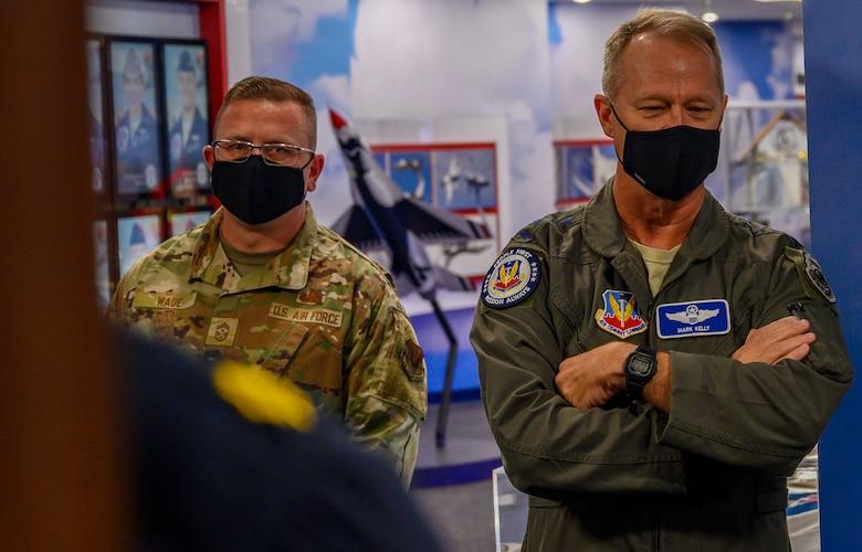 Airmen stand in a hallway.
