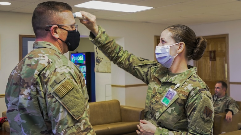Airman gets his temperature checked by another Airman.