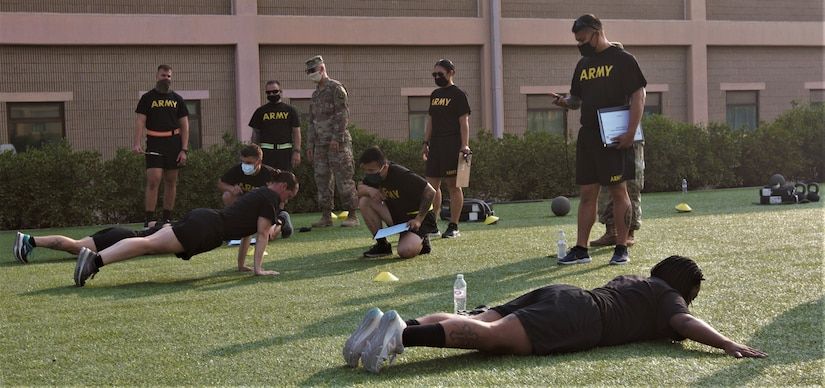 Soldiers from the 311th Expeditionary Sustainment Command, 3rd Medical Command, 401st Army Field Support Brigade, and the 304th Sustainment Brigade perform joint training on the Hand Release Push-up in preparation for executing and grading the Army Combat Fitness Test at the Area Support Group-Kuwait Field Oct. 6, 2020. This training was conducted as part of the 1st Theater Sustainment Command's ACFT familiarization and grader validation and is ensuring readiness for the Army units currently serving at Camp Arifjan, Kuwait. (U.S. Army Photo by Spc. Andrew E. Figueroa)