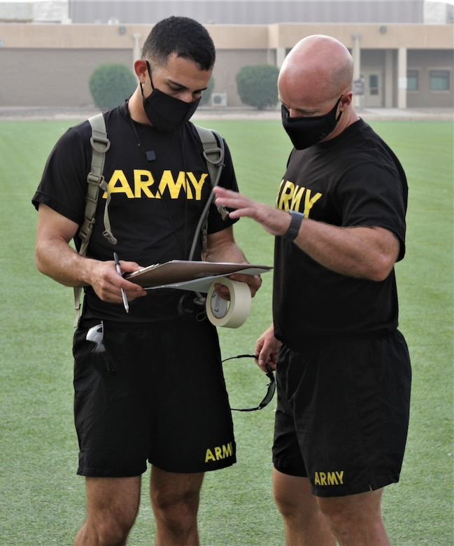 1st Lt. Matthew Zecchini (left), communications officer, 311th Expeditionary Sustainment Command, discusses the Army Combat Fitness Test grading criteria with Staff Sgt. Eric Smith, G3 training noncommissioned officer, 1st Theater Sustainment Command, during ACFT familiarization and grader validation at the Area Support Group-Kuwait Field at Camp Arifjan, Kuwait, Oct. 6, 2020. (U.S. Army Photo by Spc. Andrew E. Figueroa)